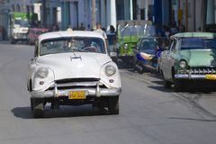 Cuban person drives vintage American car at the street of Pinar del Rio, Cuba. Royalty Free Stock Photos