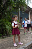 A cuban pupil. Dressed with her white and burgundy uniform is waiting for the bus Royalty Free Stock Photos