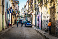 Cuban street view with people and cuban flag,  in La Havana, Cuba. Cuban street view with people and cuban flag, on december 26, 2016, in La Havana, Cuba Royalty Free Stock Photos