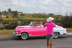 Cuban taxi driver photographing tourists on his pink classic Chevrolet. Havana, Cuba - March 12, 2018: Taxi driver photographing tourists on his pink classic Stock Photos