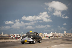 Cuban Taxi on the Malecon Havana Cuba. HAVANA, CUBA - MAY 18, 2011: Classic black American taxi drives alongside crowds of Cubans relaxing on the Malecon in Royalty Free Stock Photos