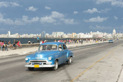Cuban Taxi on the Malecon Havana Cuba. HAVANA, CUBA - MAY 18, 2011: Classic blue American taxi drives alongside crowds of Cubans relaxing on the Malecon in Royalty Free Stock Image