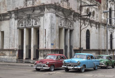 Cuban taxis passing under an old church in Havana,. 3 classic american cars passing under an old church in Havana, Cuba royalty free stock image