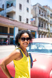Cuban woman and an old red car in Havana, Cuba Royalty Free Stock Photography