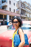Cuban woman and an old red car in Havana, Cuba Stock Photography
