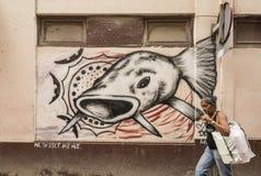 Cuban woman passing wallpainting big fish Havana Royalty Free Stock Photography