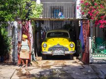 Cuban women with yellow head scarf next to a matching car. Women with yellow  headscarf in front of bright yellow oldtimer in a suburb of Havana, Cuba Stock Photo