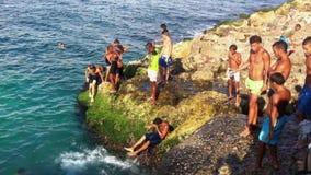 Cubanos jovenes que saltan en el mar en Havana Cuba almacen de video