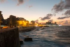 Cubans contemplate the sunset in the famous malecon in Havana, C. HAVANA, CUBA- JANUARY 15 2017: Sunset at Malecon, the famous Havana promenades where Habaneros Royalty Free Stock Image