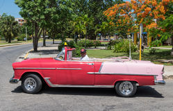 Cubans drives in your red american Oldtimer in Varadero.  Stock Photography