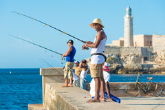 Cubans fishing in front of the famous El Morro castle in Havana. Cubans fishing in front of the famous El Morro castle, a worldwide known cuban landmark Royalty Free Stock Image