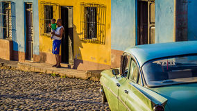 Cubans with oldtimer taxi in Trinidad. Trinidad, Cuba on December 30, 2015: Cuban father with son next to taxi in morning light Stock Image