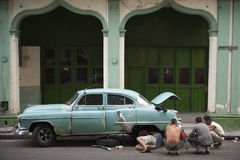 Cubans Repairing Classic American Car Havana Cuba. HAVANA, CUBA - MAY 18, 2011: Cubans work together to repair a classic American car sits on a street in Habana Royalty Free Stock Photography