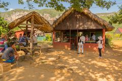 Cubans and tourists relaxing. Vinales, Cuba - December 5, 2017: Cubans and tourists relaxing at farm bar Royalty Free Stock Photography