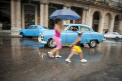 Cubans and Vintage American Cars Havana Cuba. HAVANA, CUBA - JUNE 13, 2011: Cuban mother and child cross the street in front of vintage American taxi car on a Stock Images
