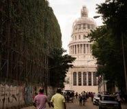Cubans walking towards capitol in Havana. Havana, Cuba on December 23, 2015: Cuban people walking towards capitolio goverment building Stock Photo