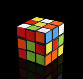 Cube on a black background. Different colors. Puzzle. Reflection from a surface Royalty Free Stock Photos