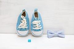 Cube bleu avec le numéro 1 et espadrilles bleues du ` s d'enfants sur un blanc Photo stock