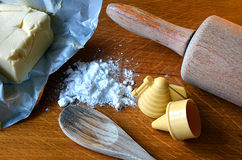 Cube of butter, candy molds and icing sugar on wooden table. Cube of butter, candy molds, icing sugar and rolling-pin on wooden kitchen table Stock Image