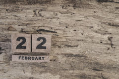 Cube calendar for february on wooden background. With copy space Royalty Free Stock Photo