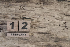 Cube calendar for february on wooden background. With copy space Royalty Free Stock Image