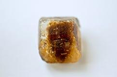 Cube caramélisé en sucre de canne sur le blanc Photos stock