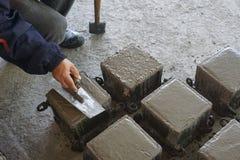 Cube a carcaça concreta pelo molde de aço e o trabalhador que termina a superfície superior pela pá de pedreiro Imagens de Stock