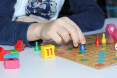 Cube, chips, wooden figures, a bright field for the game stock photos