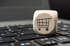 Cube dice on a keyboard with a cart, online shopping royalty free stock image