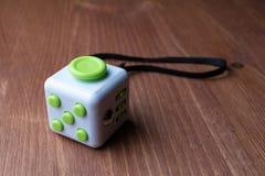 Cube en personne remuante avec les boutons verts sur une table en bois Images stock
