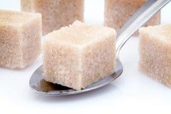 Cube et cuillère en sucre de Brown Photos stock