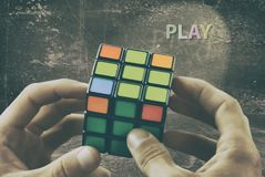 Cube in the hands of a man against the background of a vintage wall. Play the game royalty free stock images