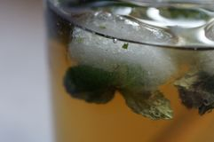 A cube of ice in ice tea. stock photos
