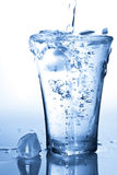 cube la glace en verre éclaboussant l'eau Images stock