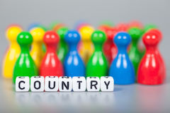 Cube Letters show country  in front of unsharp ludo figures Stock Photo