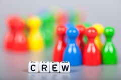 Cube Letters show crew  in front of unsharp ludo figures Royalty Free Stock Photos