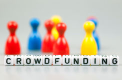 Cube Letters show crowdfunding  in front of unsharp ludo figures Royalty Free Stock Images