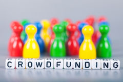 Cube Letters show crowdfunding  in front of unsharp ludo figures Royalty Free Stock Photography