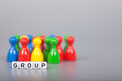 Cube Letters show Group  in front of unsharp ludo figures Stock Photos
