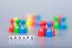Cube Letters show Groups  in front of unsharp ludo figures Royalty Free Stock Photography