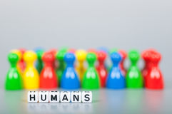 Cube Letters show humans  in front of unsharp ludo figures Royalty Free Stock Image