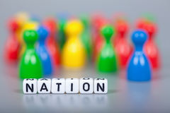 Cube Letters show nation  in front of unsharp ludo figures Royalty Free Stock Images