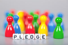 Cube Letters show pledge  in front of unsharp ludo figures Stock Photos