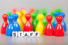Cube Letters show staff  in front of unsharp ludo figures Stock Images
