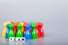 Cube Letters show team in front of unsharp ludo figures Stock Photos
