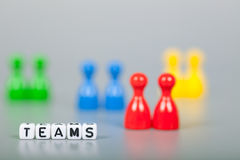 Cube Letters show teams  in front of unsharp ludo figures Stock Photography