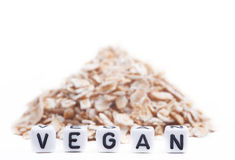 Cube Letters Show Vegan  in Front of oat flakes Royalty Free Stock Image