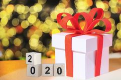 Cube number 2020 and white gift box. Cube number 2019 and white gift box with red ribbon, celebration concept royalty free stock photography