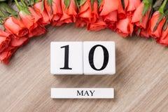 Cube o calendário da forma para o 10 de maio na tabela de madeira com rosas Fotos de Stock Royalty Free