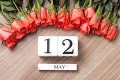 Cube o calendário da forma para o 12 de maio na tabela de madeira com rosas Imagens de Stock